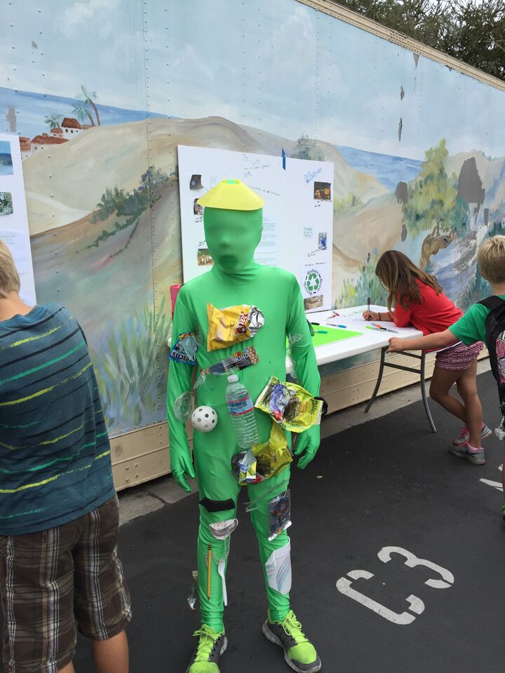 Child wearing green body suit with trash attached